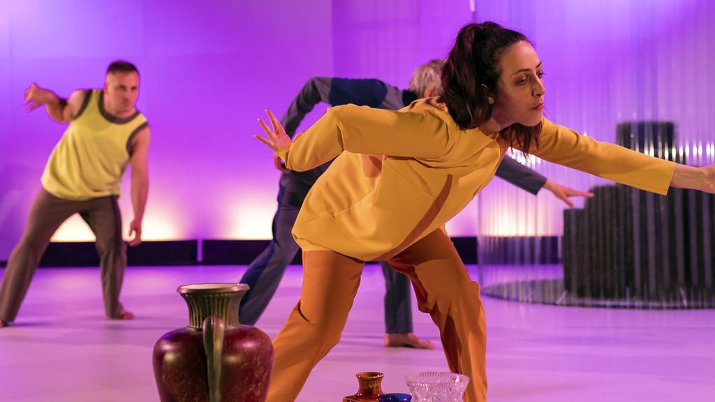 Szenenfoto aus einer Auffuehrung: Drei Menschen tanzen auf einer Theaterbühne. Im Vordergrund Blumenvasen.