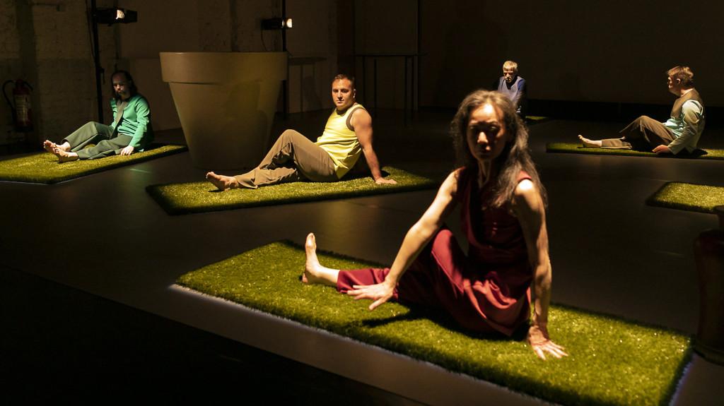 Szenenfoto aus einer Auffuehrung: Fünf Personen sitzend auf einer Theaterbühne.