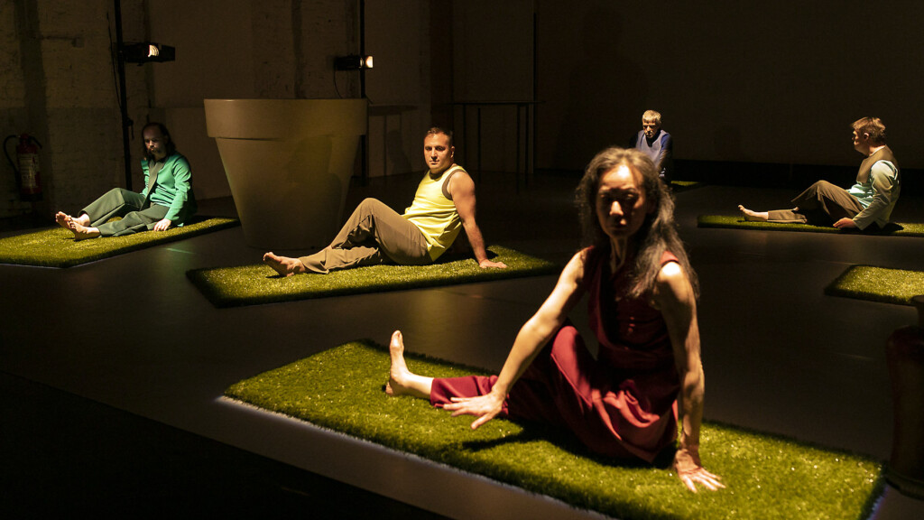 Scene photo of a performance: Five people are sitting on a stage.