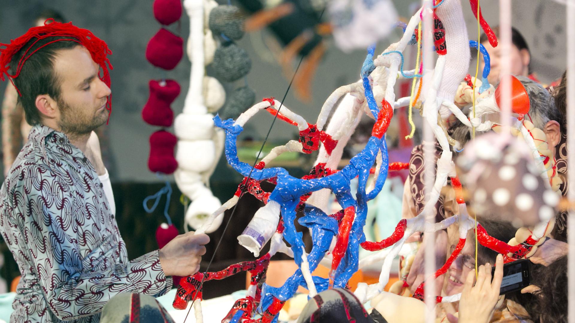 Szenenfoto aus einer Auffuehrung: Links steht ein Mann mit einem schlafanzugähnlichen Hemd mit einem Büschel roter Wolle auf dem Kopf vor einem fast bildfüllenden Gebilde aus roten, blauen und weißen Kabeln. Rechts hinten ist unscharf der Kopf einer Frau zu erkennen.
