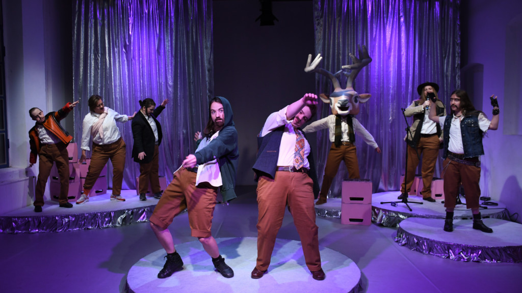 Scene photo of a performance: two people in the foreground on a theater stage. In the background, people with and without a deer mask.