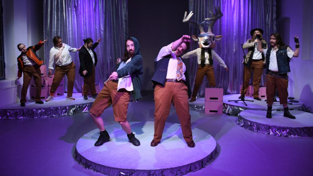 Foto einer Auffuehrung: Zwei Personen im Vordergrund auf einer Theaterbühne. Im Hintergrund Menschen mit und ohne Hirschmaske.