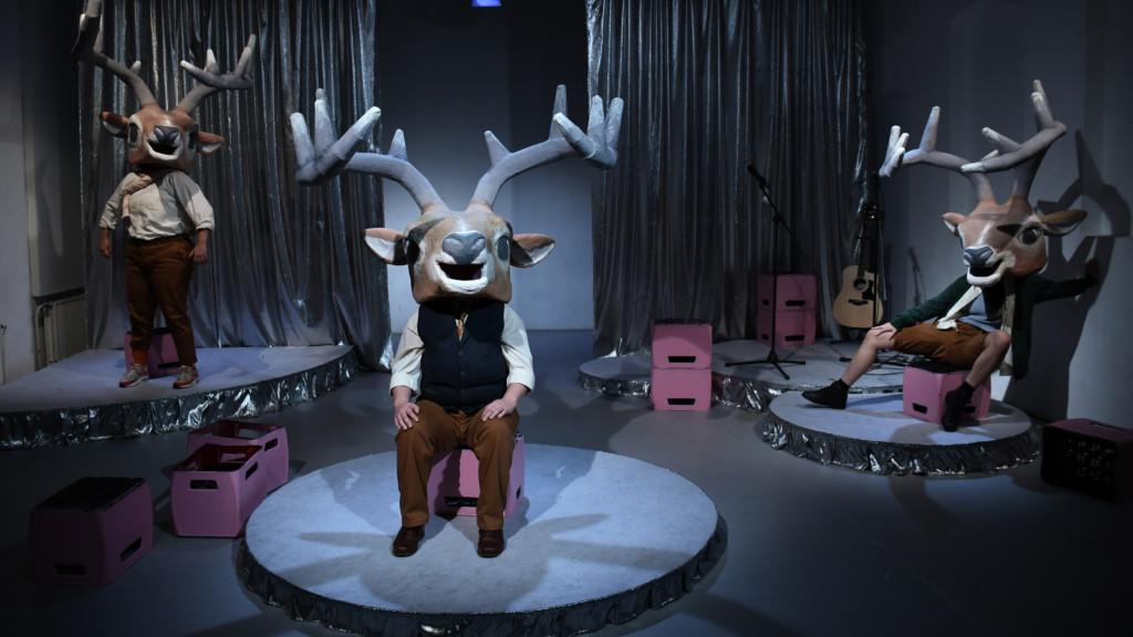 Szenenfoto einer Auffuehrung: Drei Personen mit einer Hirschmaske auf einer Bühne.