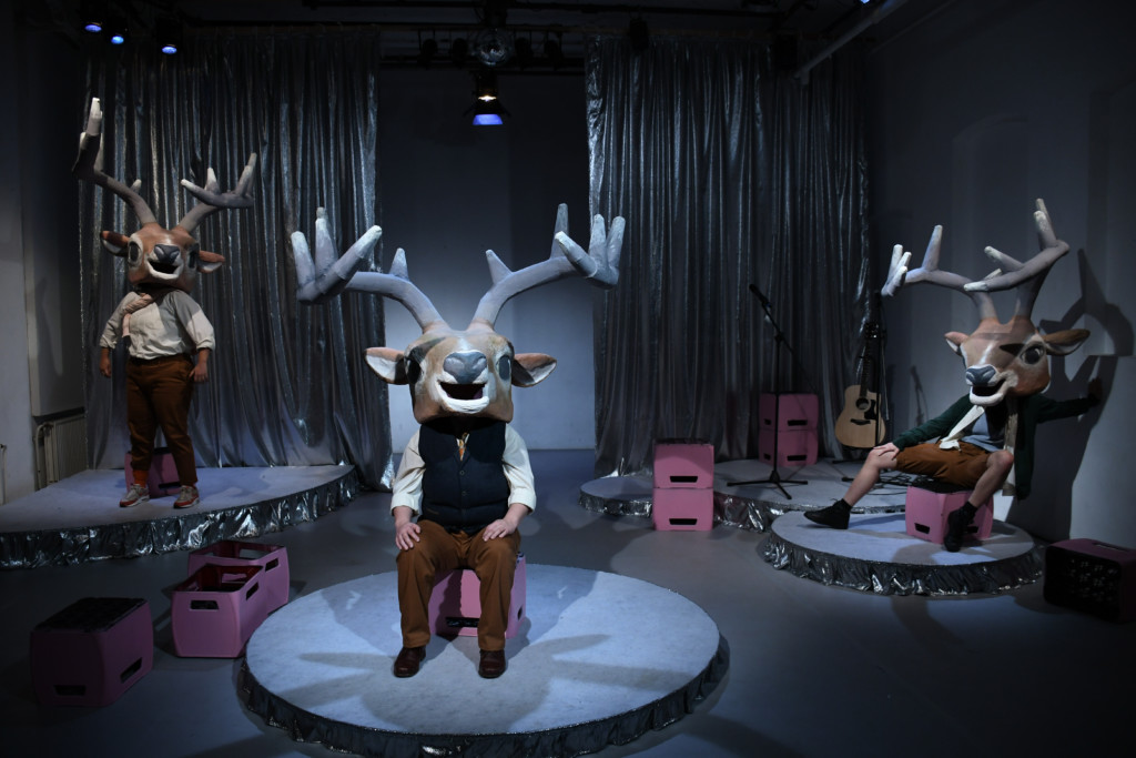 Scene photo of a performance: three actors wear deer masks with antlers and are on separate bases.