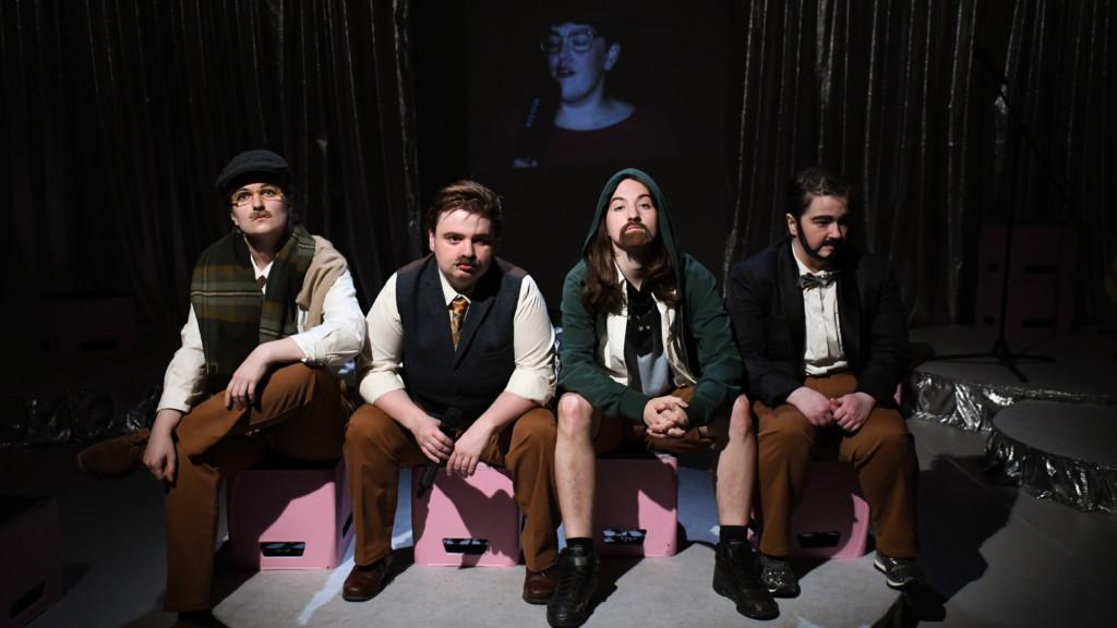 Szenenfoto einer Auffuehrung: Vier Personen nebeneinander sitzend auf einer Bühne.