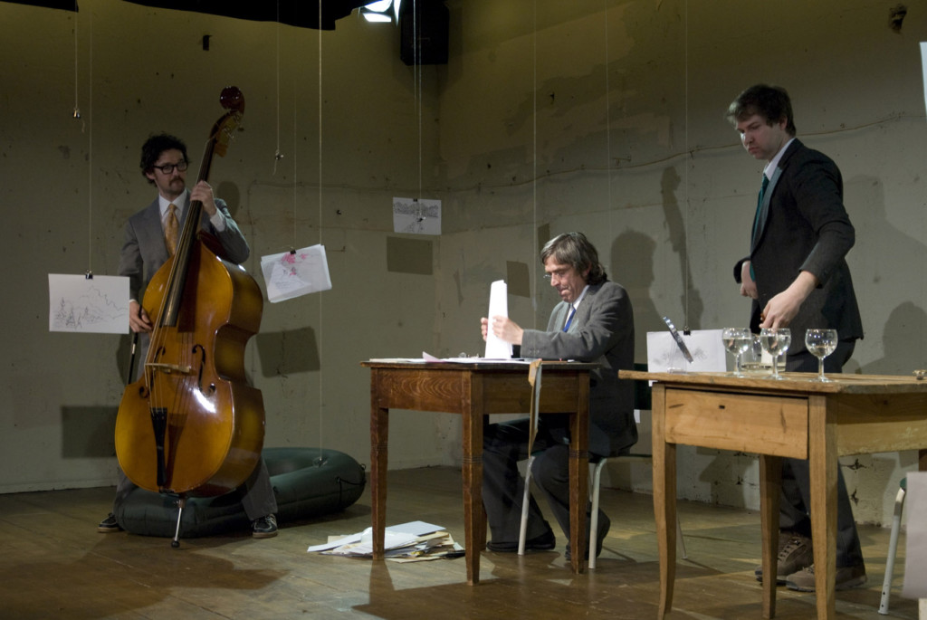 Scene photo of a performance: On the left side a man with a contra bass. On the right side are two men near wood tables.