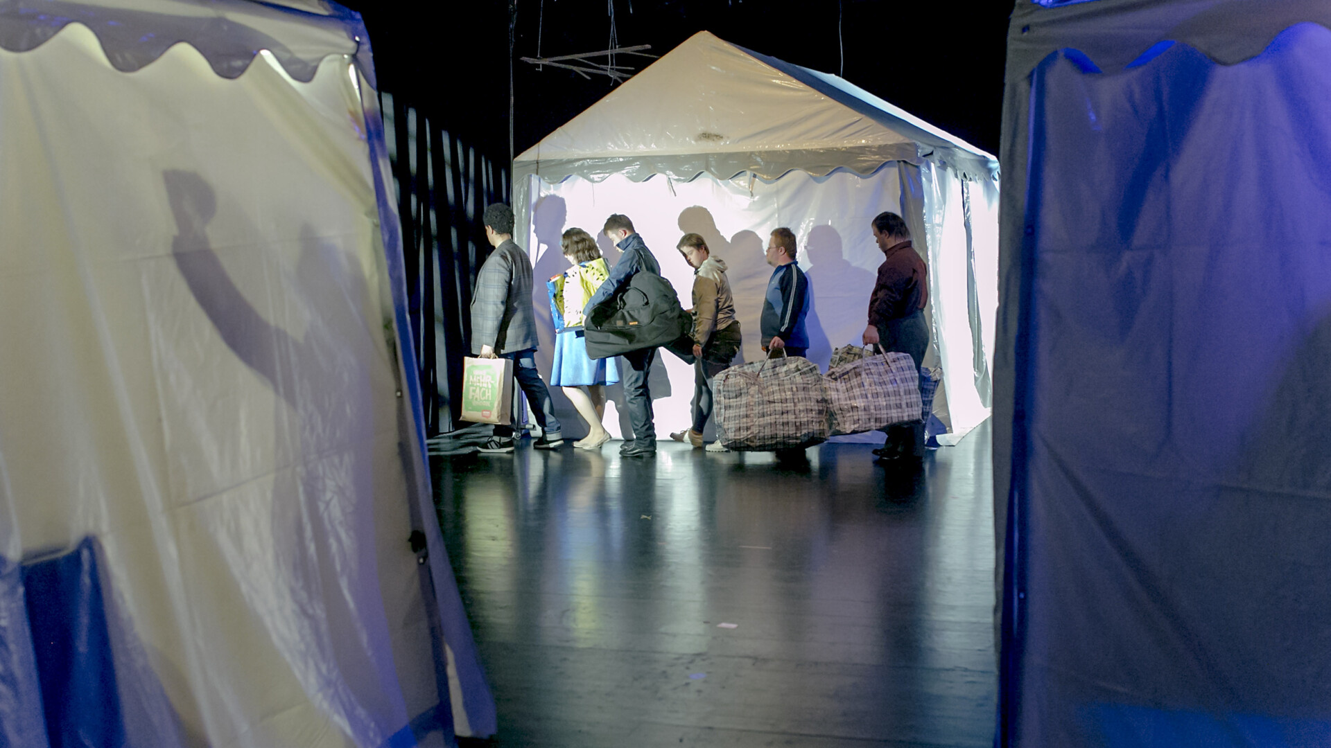 Scene photo of a performance: Three white party tents, 6 people mit bags in the background.