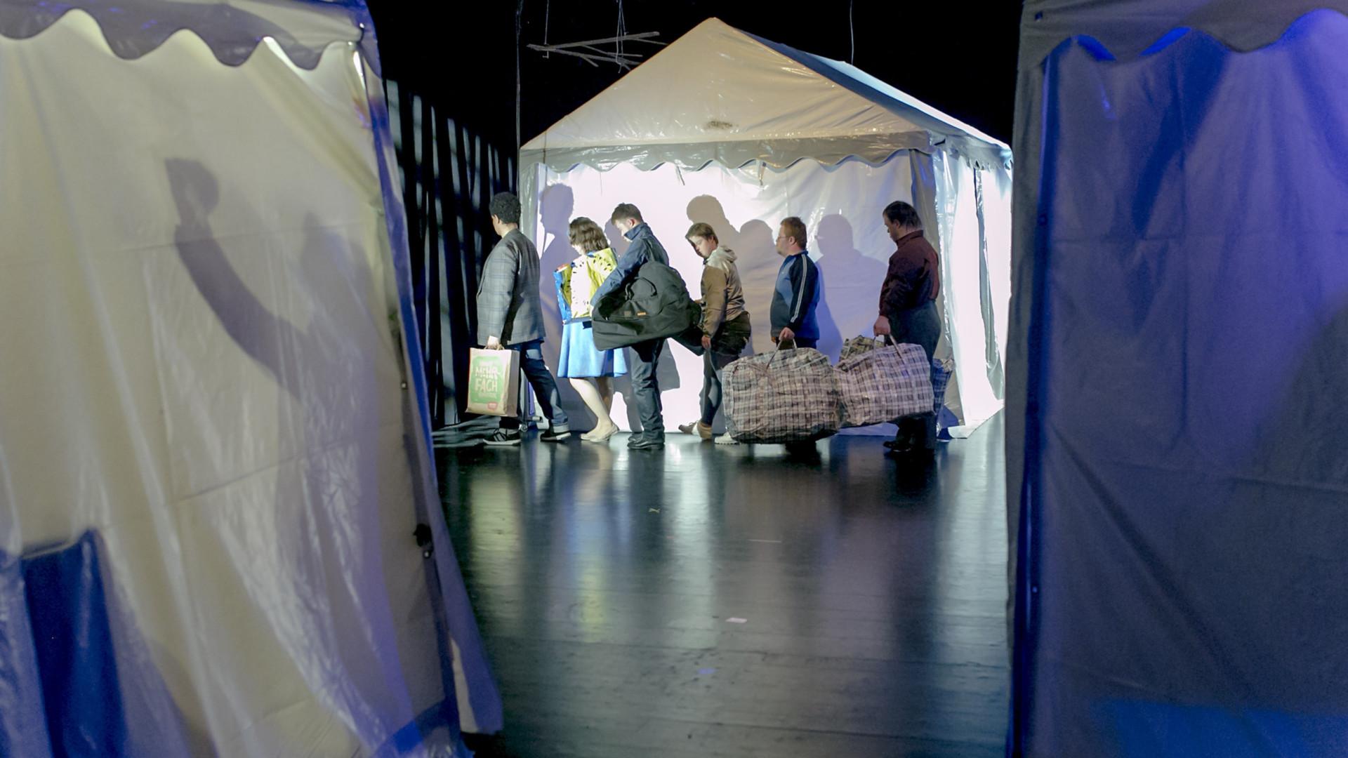 Szenenfoto aus einer Auffuehrung: Drei weisse Partyzelte, zwei angeschnitten im Vordergrund, eines im Hintergrund. Vor dem hintern Zelt geht eine Gruppe von 6 Personen hintereinander entlang, in Alltagskleidung, alle mit großen Tüten und Taschen.