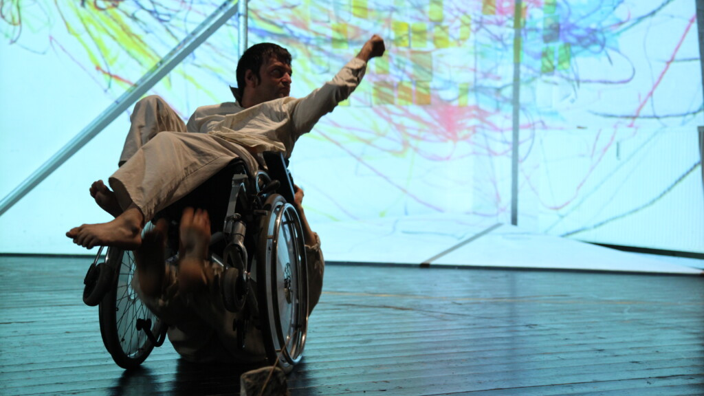 Scene photo of a performance: A man in a wheelchair in front of something which looks like map an a stage.