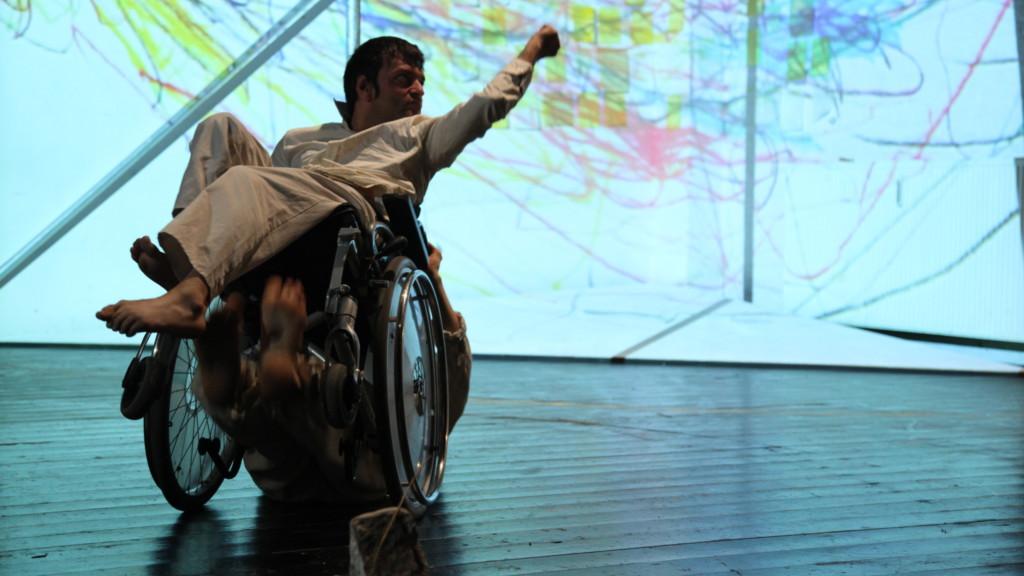 Szenenfoto aus einer Auffuehrung. Vor einem hellen, mit bunten Strichen vollgekritzeltem Hintergrund sitzt ein Mann mit hochgerecktem Arm in einem Rollstuhl. Der Rollstuhl ist leicht nach oben gekippt. Darunter sind schemenhaft die Füße eines weiteren Mannes zu sehen.