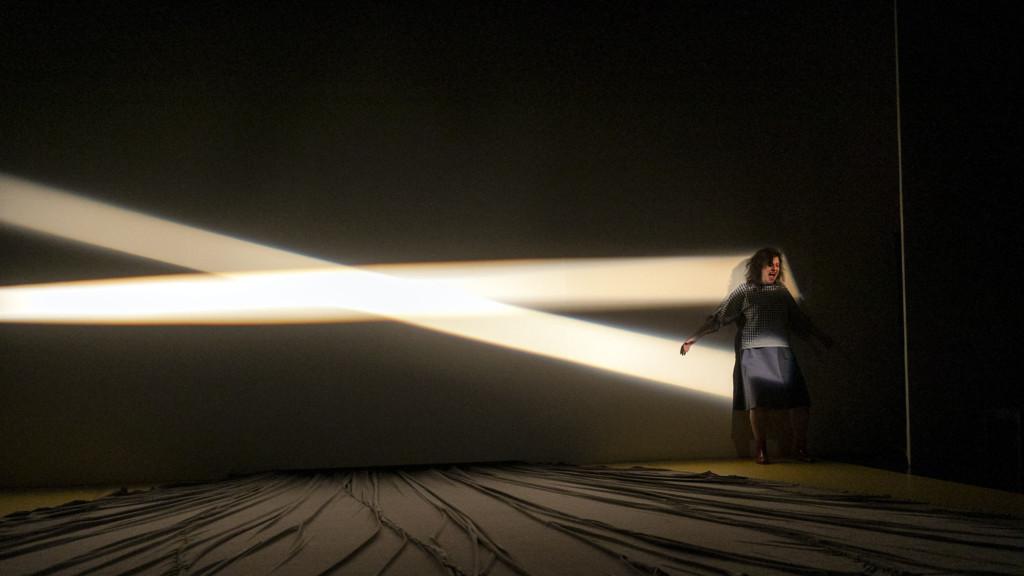 Szenenfoto aus einer Auffuehrung: Eine schreiende Frau steht auf einer Theaterbuehne.