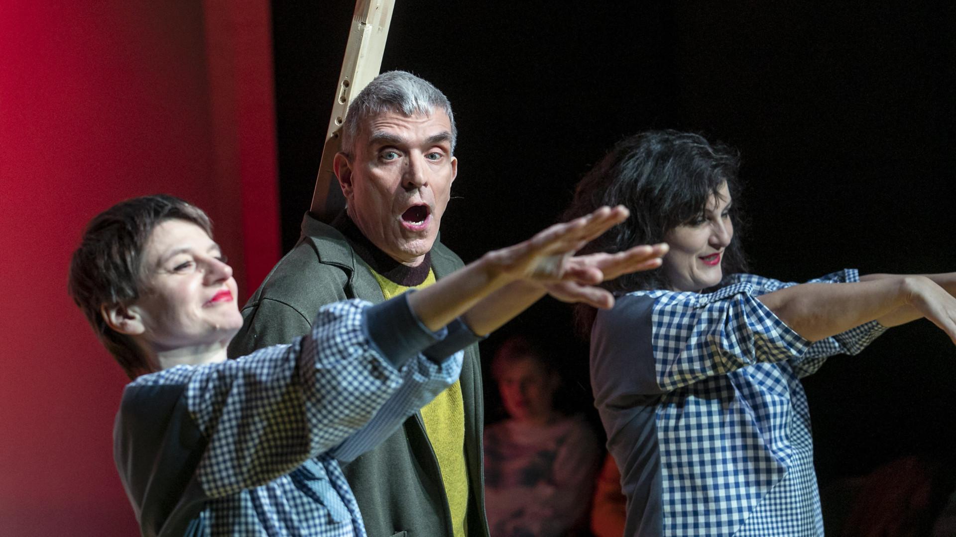 Szenenfoto aus einer Auffuehrung: Zwei Frauen und ein Mann auf einer Theaterbühne.