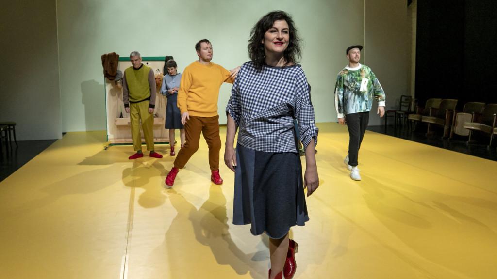 Szenenfoto aus einer Auffuehrung: Mehrere Personen sind auf der Bühne. Im Vordergrund eine Frau.