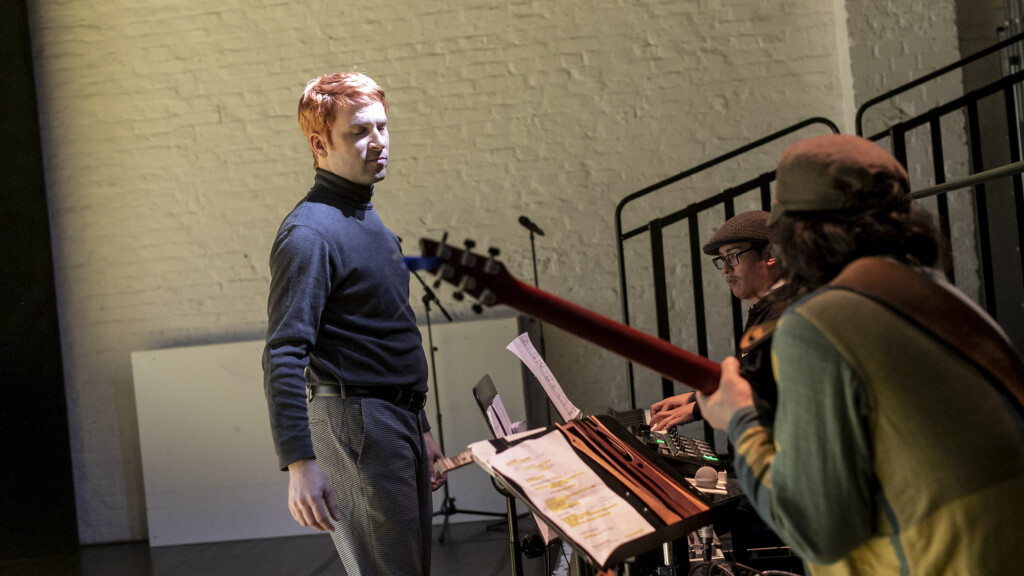 Scene photo of a performance: There men on a stage. Two are playing an instrument. One is standing.