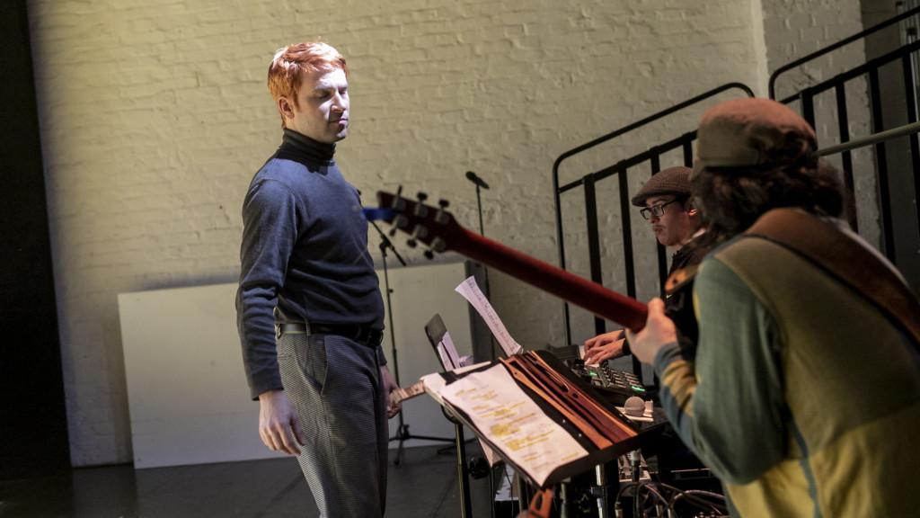 Szenenfoto aus einer Auffuehrung: Drei Männer auf der Bühne. Davon sind zwei Musiker.