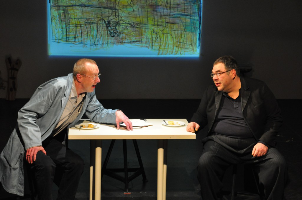 Photo from a performance: Two men talk at a table on a theater stage.