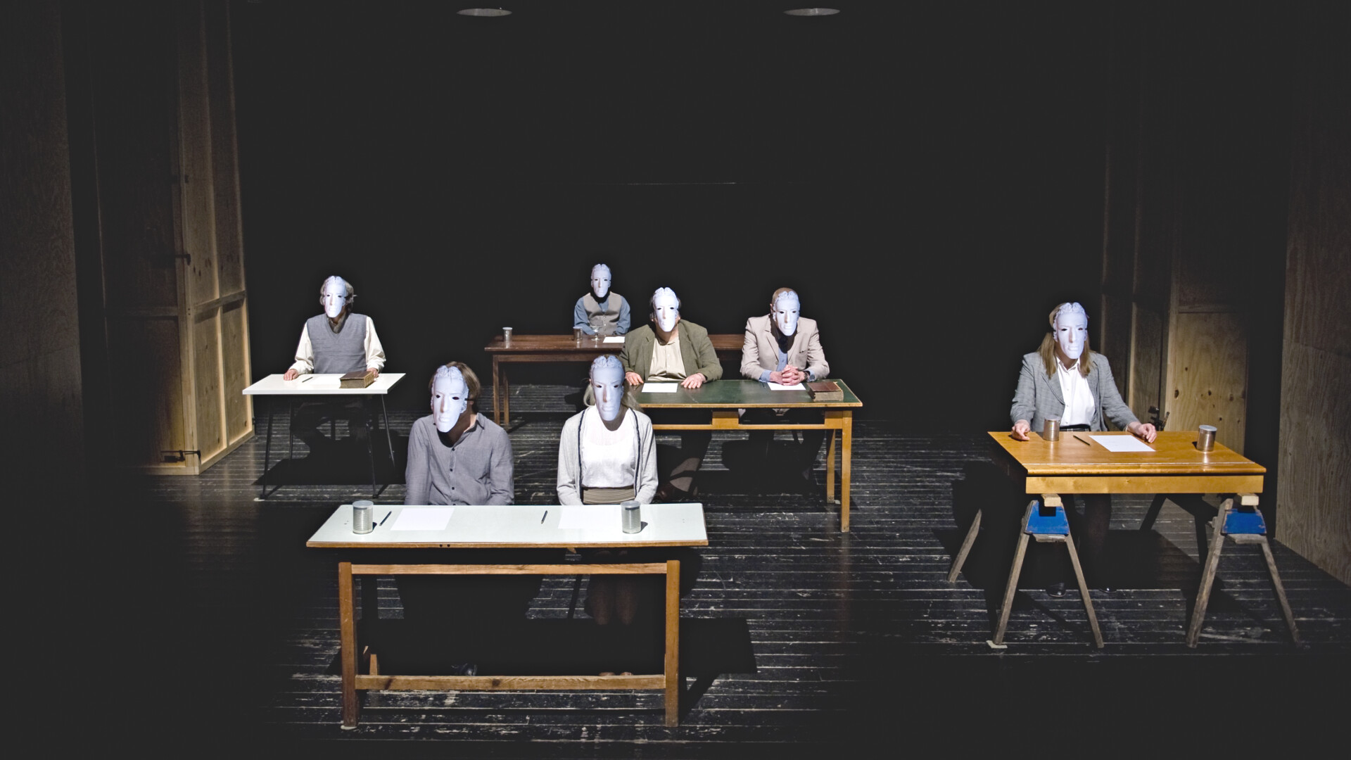 Five tables are on the stage. At every table there is a person sitting wearing modest clothes and a grey mask. At the table in the middle there are two people sitting.