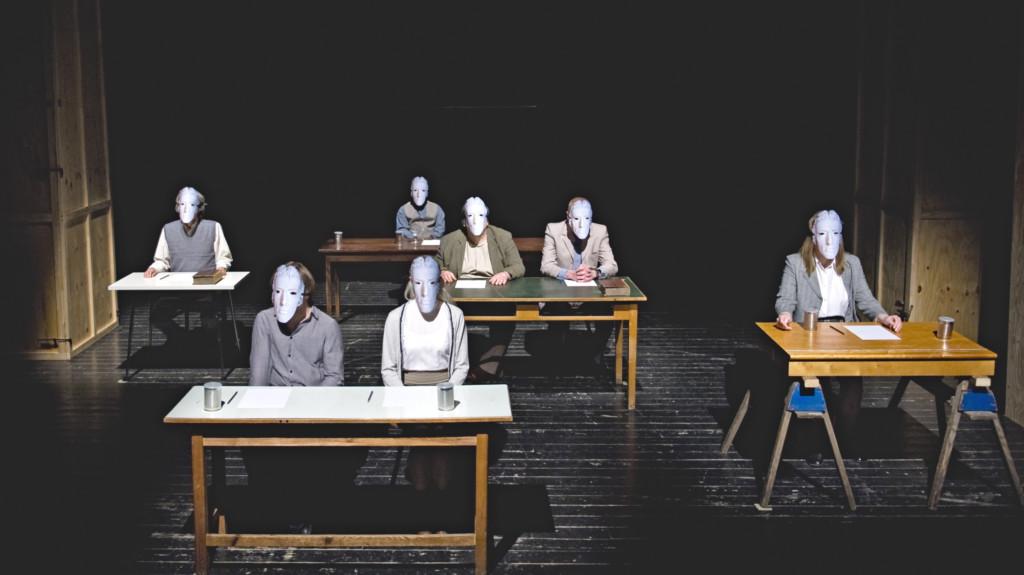 Szenenfoto aus einer Auffuehrung: Fünf Tische über das ganze Bild verteilt. Hinter jedem Tisch sitzt eine Person in schlichter Kleidung. Alle haben graue Masken auf. Am Tisch in der Mitte sitzen zwei Personen.