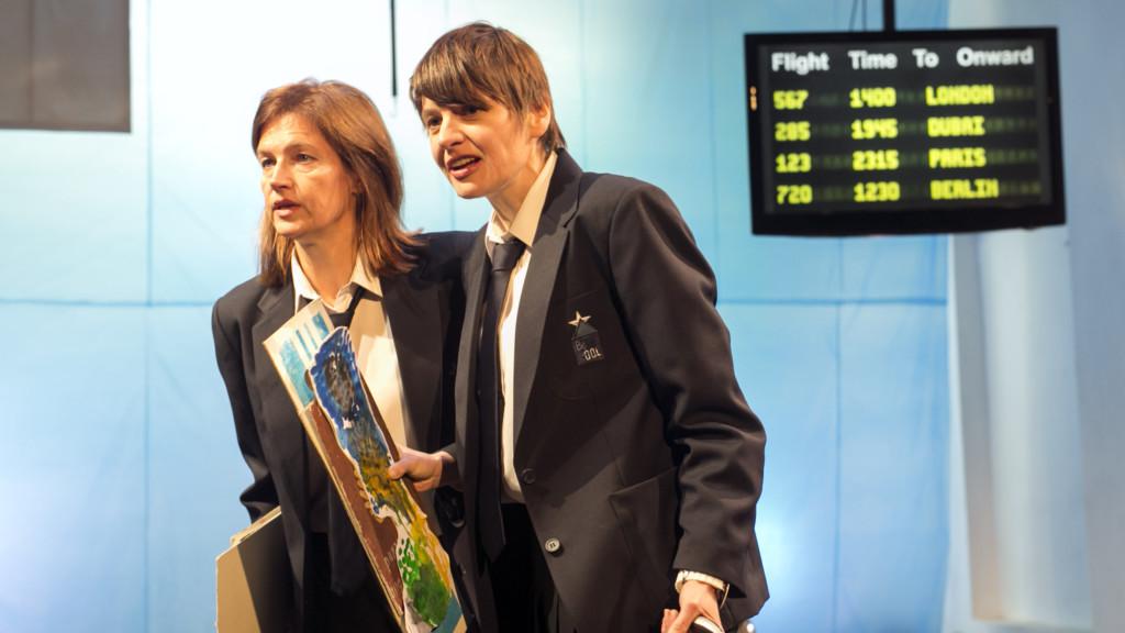 Szenenfoto einer Auffuehrung: Zwei Frauen mit Bilder auf einer Bühne. Im Hintergrund eine Anzeigetafel.
