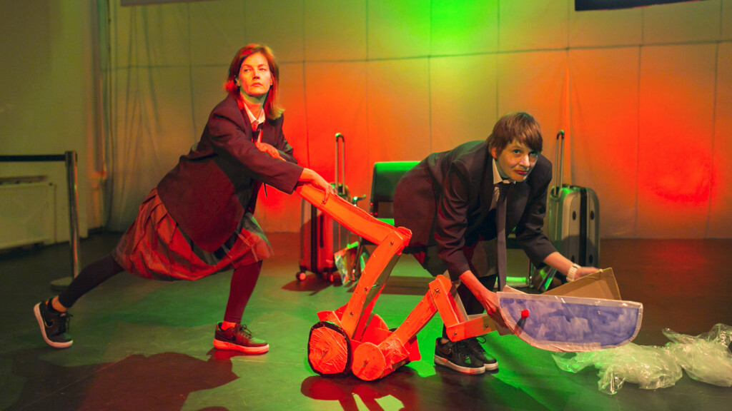 Scene photo of a performance: Two women on a stage pushing a digger.