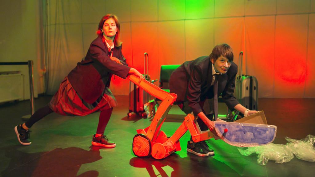 Szenenfoto einer Auffuehrung: Zwei Frauen auf einer Bühne schieben einen Pappbagger.
