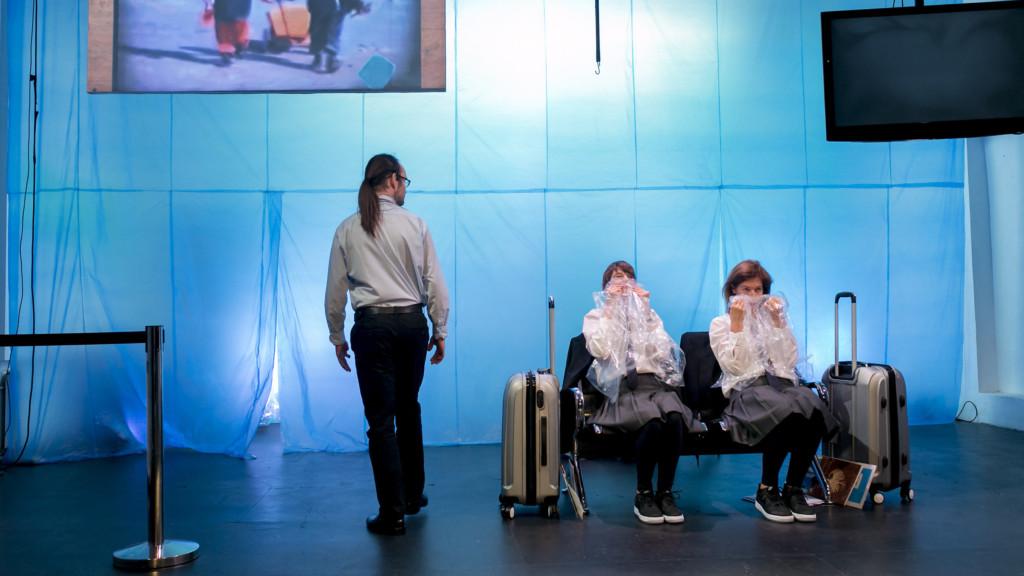 Szenenfoto einer Auffuehrung: Drei Personen auf einer Bühnen. Zwei Frauen sitzen und ein Mann steht mit dem Rücken zum Zuschauer.