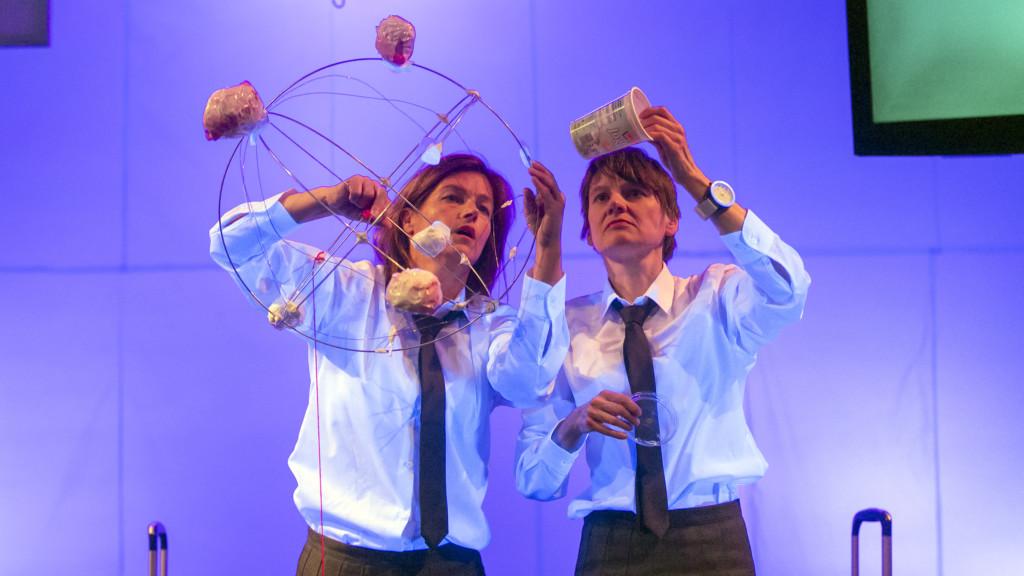 Szenenfoto einer Auffuehrung: Zwei Frauen mit Schlips nebeneinander auf einer Bühne.