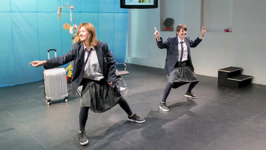 Szenenfoto einer Auffuehrung: Zwei Frauen lachend auf einer Bühne. Im Hintergrund ein Koffer, ein Bildschirm und andere Gegenstände