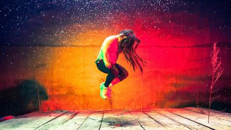 Szenenfoto aus einer Auffuehrung: Grell rot/orangener Hintergrund, ein Bretterboden, rechts eine abgestorbene Pflanze. Ein Mann mit langen zotteligen Haaren springt hoch. Sein Gesicht ist nicht zu erkennen. Er ist nur mit schwarzen Leggins und Turnschuhen bekleidet.
