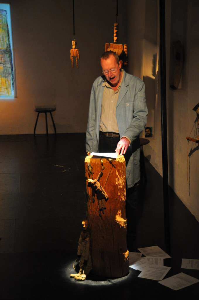 Photo from a performance: One man is reading something from a paper. wood figures are hanging behind him.