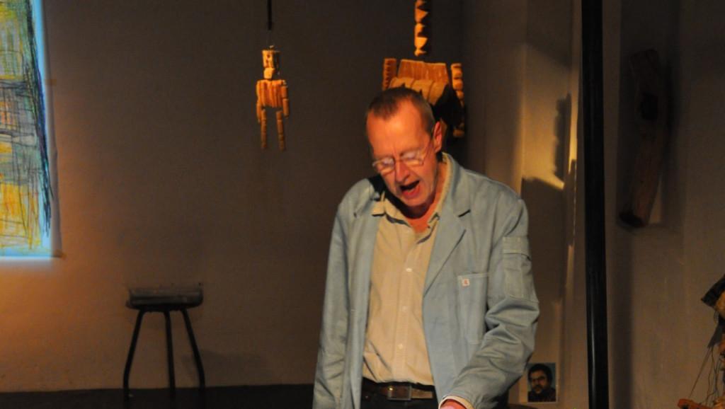 Szenenfoto aus einer Auffuehrung: Ein Mann liest etwas von einem Blatt vor. Hinter ihm haengende Holzfiguren.
