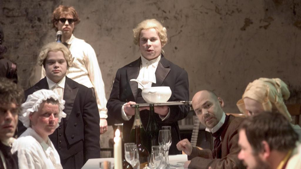 Szenenfoto aus einer Auffuehrung. 8 Menschen an einem festlich gedeckten Tisch. Alle mit Blick zur Kamera. Zwei Männer haben barocke Perücken und sind offensichtlich Bedienstete. Einer hat ein Tablett mit einer Suppenschüssel in der Hand. Alle anderen sind auch historisch gekleidet. Links im Hintergrund steht ein junger Mann, gekleidet mit einem modernen Hemd und einer Sonnenbrille vor einem Standmikrofon.