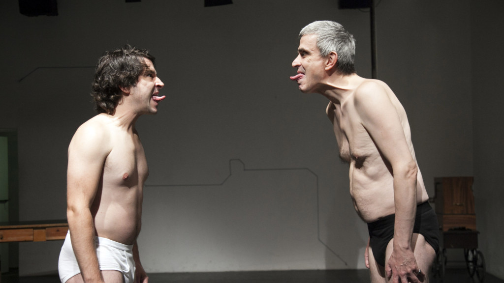 Scene photo of a performance: Two men are standing in front of each other on a stage.