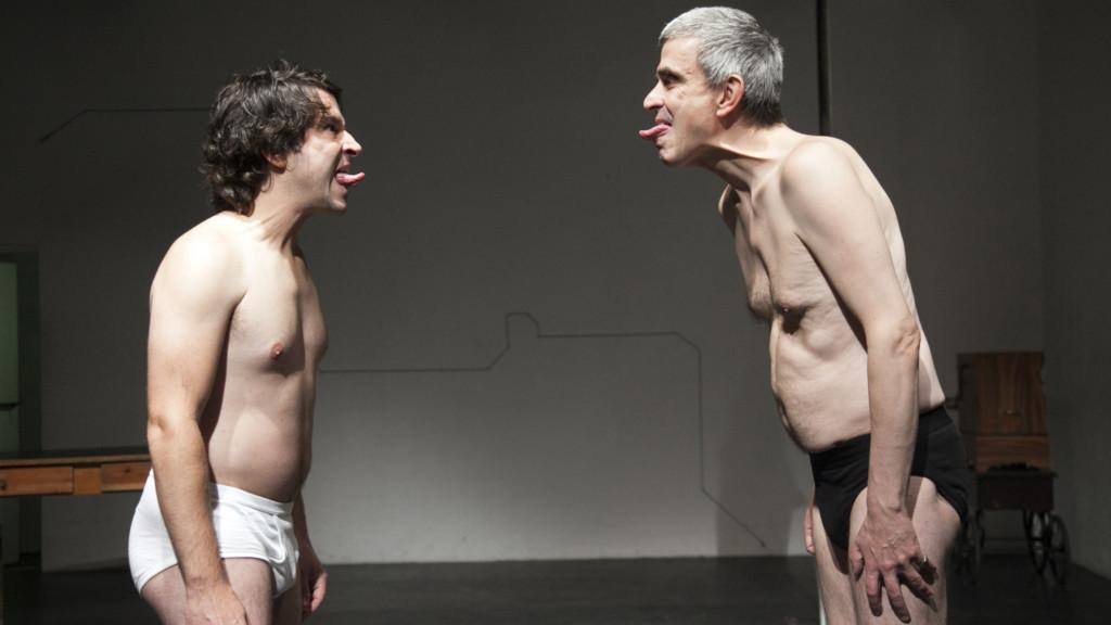Szenenfoto aus einer Auffuehrung: Zwei Maenner stehen sich in Unterhosen gegenüber auf einer Bühne.