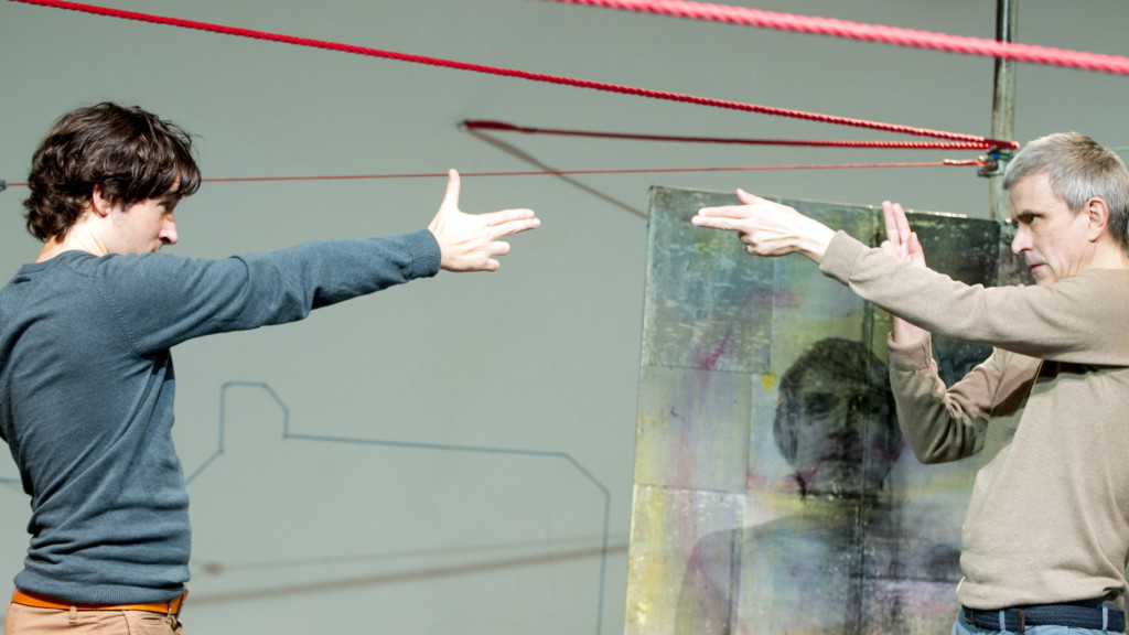 Szenenfoto aus einer Auffuehrung: Zwei Maenner stehen sich auf einer Theaterbuehne mit je einem ausgestrecktem Arm gegenüber.