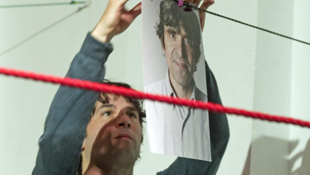 Szenenfoto aus einer Auffuehrung: Ein Mann hängt ein Bild auf eine Wäscheleine auf einer Theaterbühne.