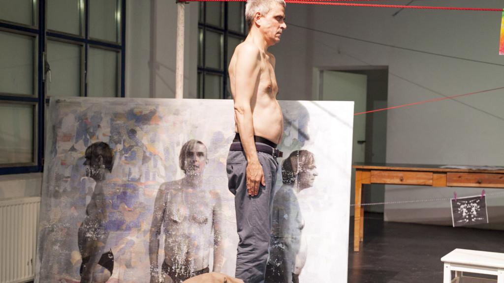 Szenenfoto aus einer Auffuehrung: Ein Mann mit geschlossenen Augen steht auf einer Theaterbühne vor einer Leinwand.