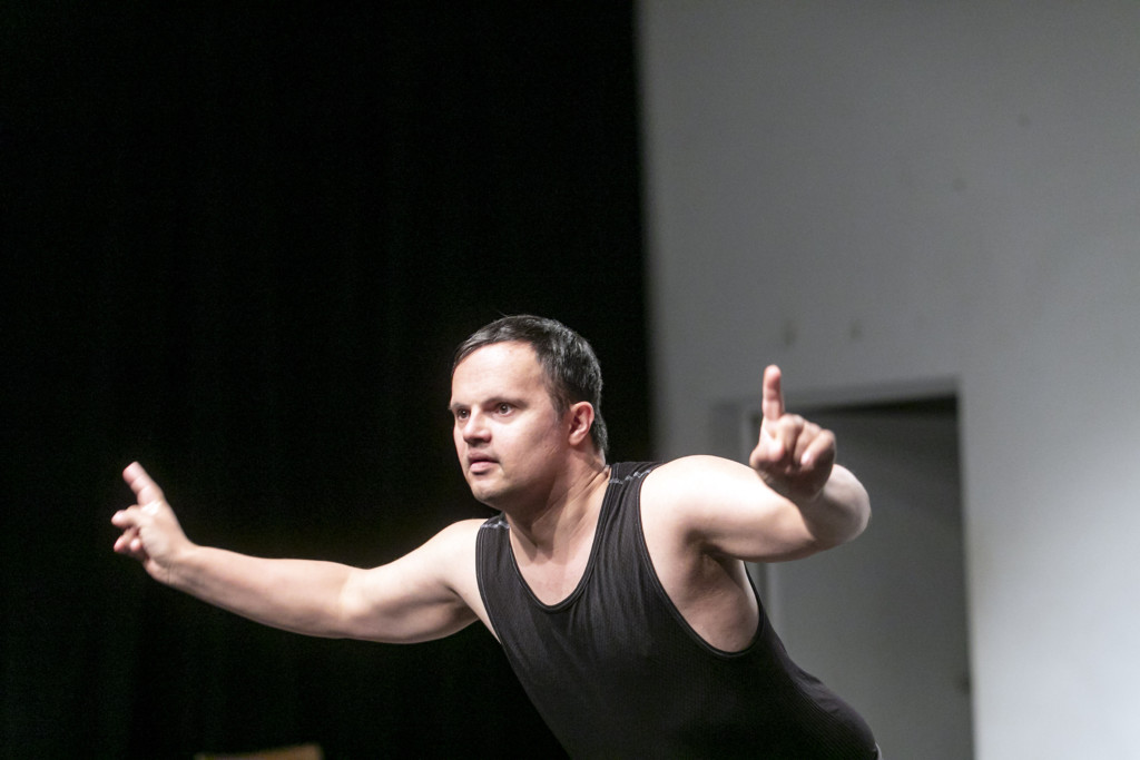 Scene photo of a performance:a man with wide-open arms on a stage.