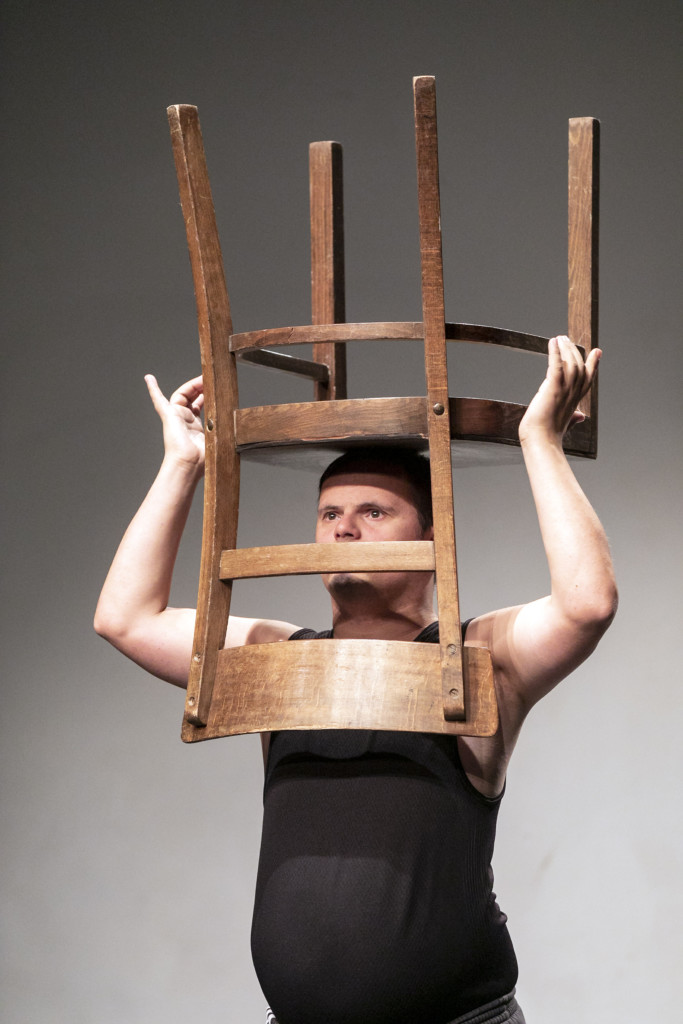 Scene photo of a performance: A man holding a chair over his head on a stage.