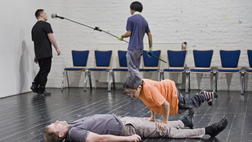 Szenenfoto aus einer Auffuehrung: Im Vordergrund liegt ein Mann. Auf ihm macht ein sehr kleiner Mann einen Handstand. Im Hintergrund ein Mann mit einer Mikrofonangel. Ein anderer Mann spricht in das Mikro.