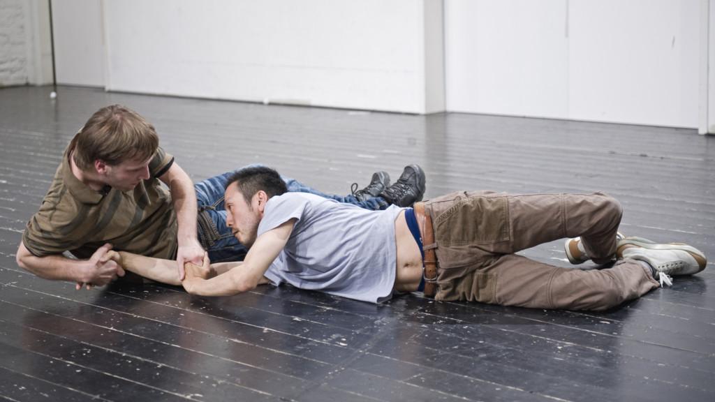 Szenenfoto aus einer Auffuehrung: Zwei Maenner in Alltagskleidung liegen auf den Boden und halten sich verschränkt an den Haenden