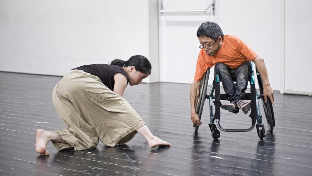 Szenenfoto: Ein Mann im Rollstuhl und eine Frau auf Knieen in Bewegung. Beide sind japanisch.
