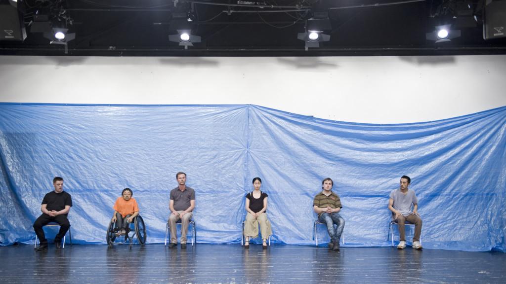 Szenenfoto aus einer Auffuehrung: 6 Menschen, davon einer im Rollstuhl, sitzen in Alltagskleidung vor einem blauen Plastikhintergrund