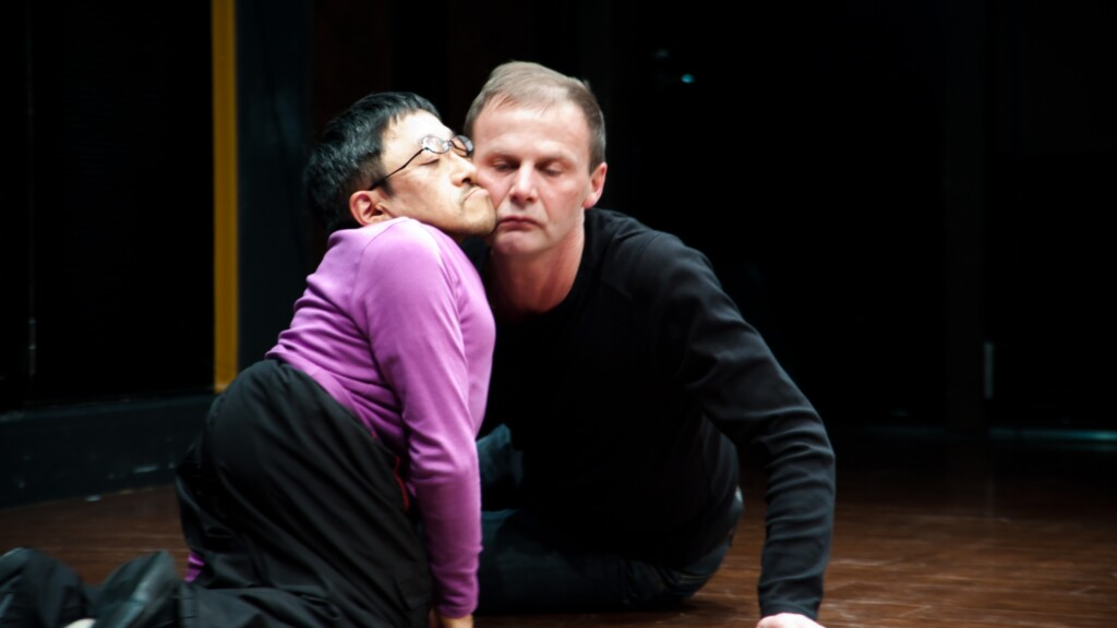 Scene photo of a performance: Two men on a stage. Their cheeks touching each other.