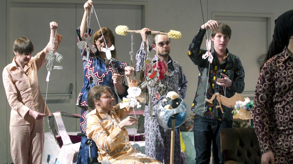 Szenenfoto aus einer Auffuehrung: Eine Gruppe buntgekleideter Menschen. In den Haenden halten sie seltsame Objekte aus Papier, die an Faeden haengen