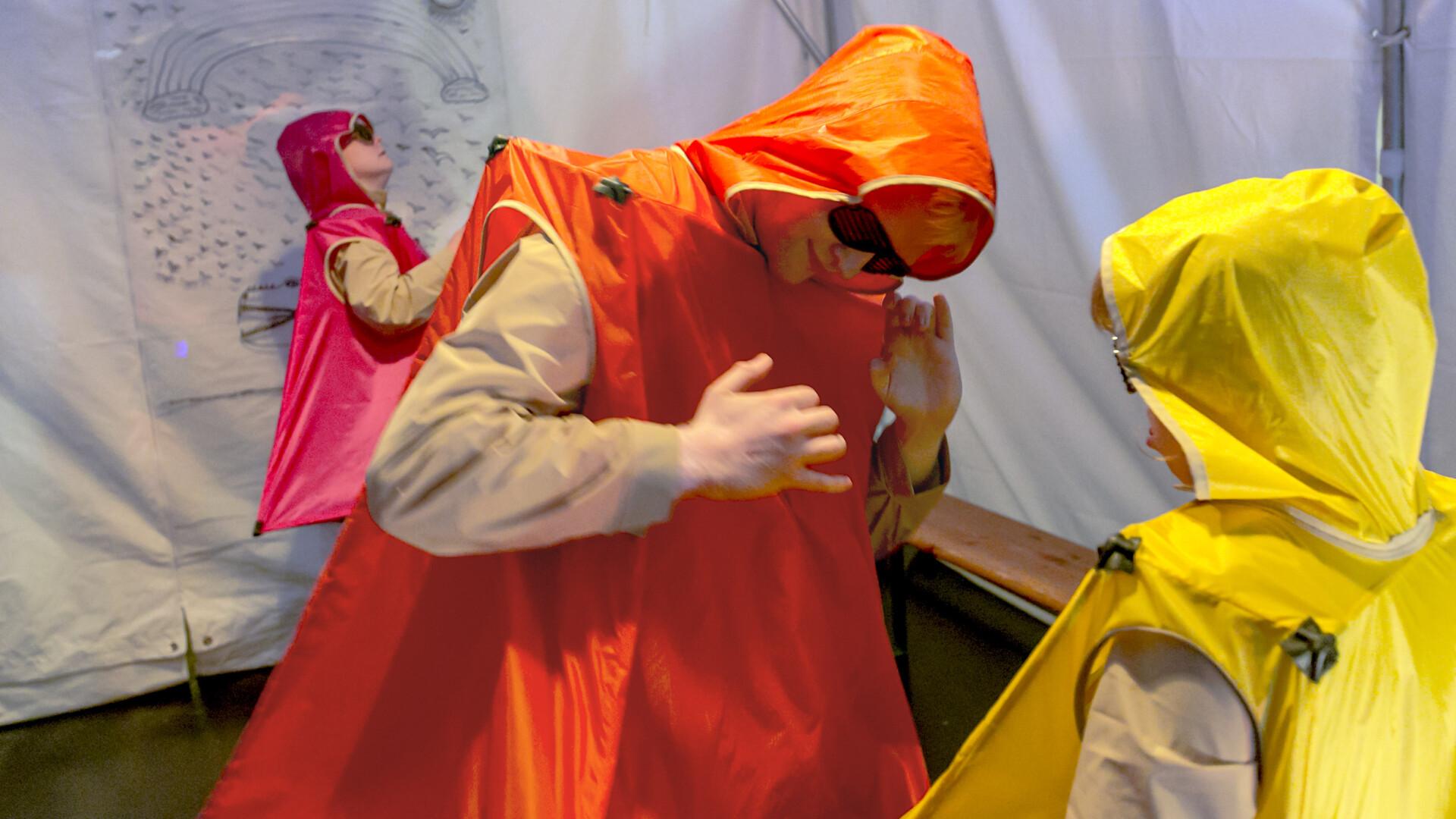 Szenenfoto aus einer Aufführung: Drei Personen in futuristisch eckigen Plastikkostümen und mit Sonnenbrille tanzen.
