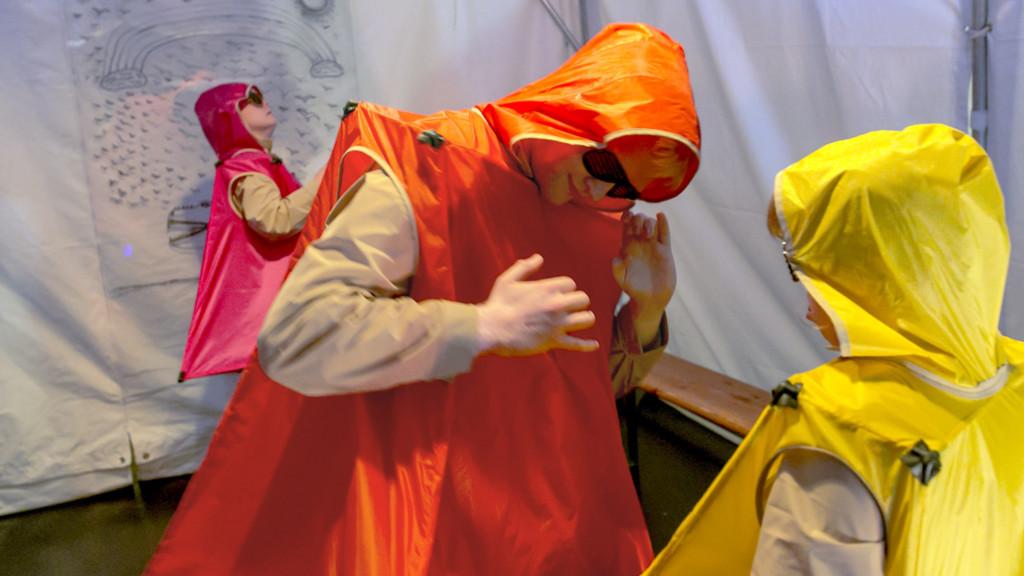 Szenenfoto aus einer Auffuehrung: Drei Personen in futuristisch eckigen Plastikkostuemen und mit Sonnenbrille tanzen.