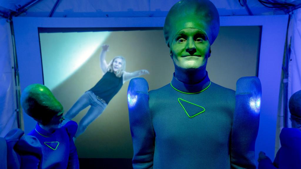 Szenenfoto aus einer Auffuehrung: Ein futuristisch gekleideter Mann mit einen verlaengerten Hinterkopf laechelt in die Kamera.