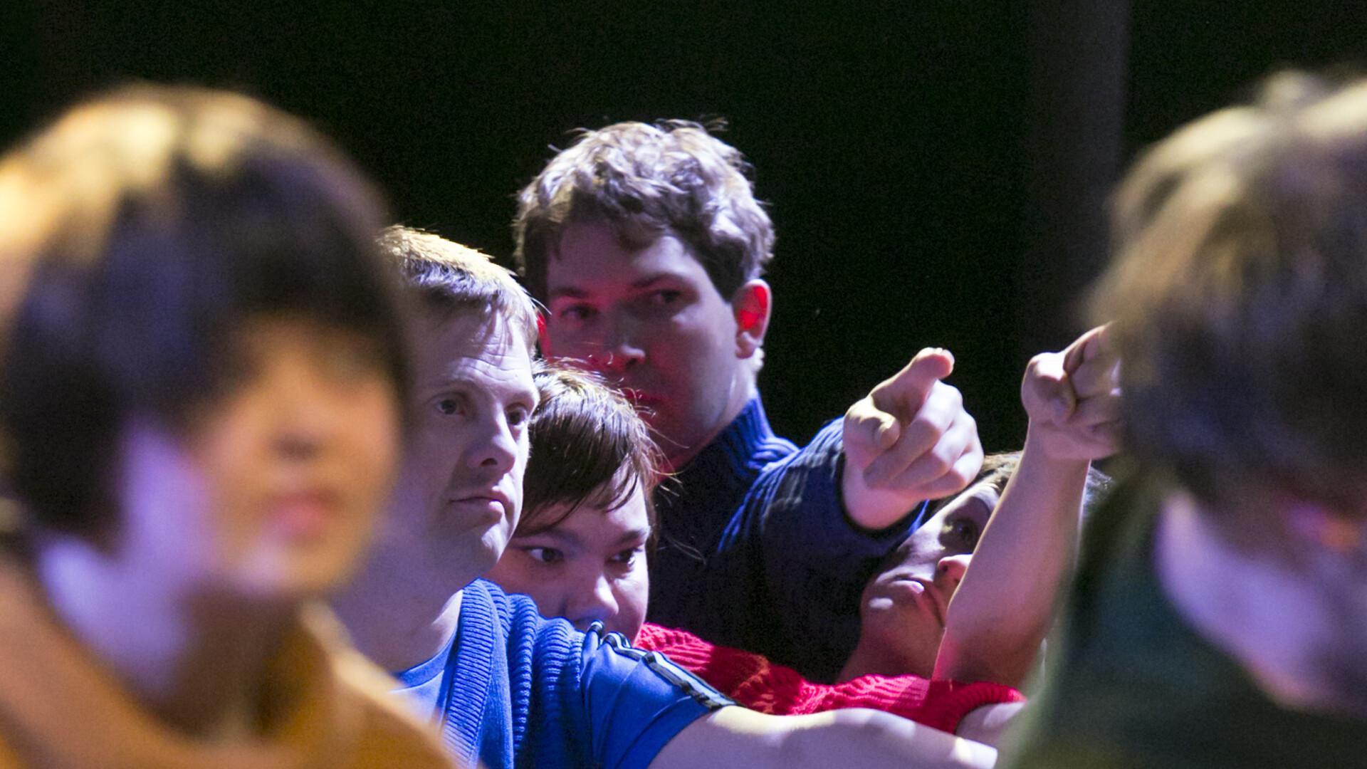 Szenenfoto aus einer Aufführung: Mehrere Menschen in Großaufnahme. Alle zeigen mit den Fingern in eine Richtung