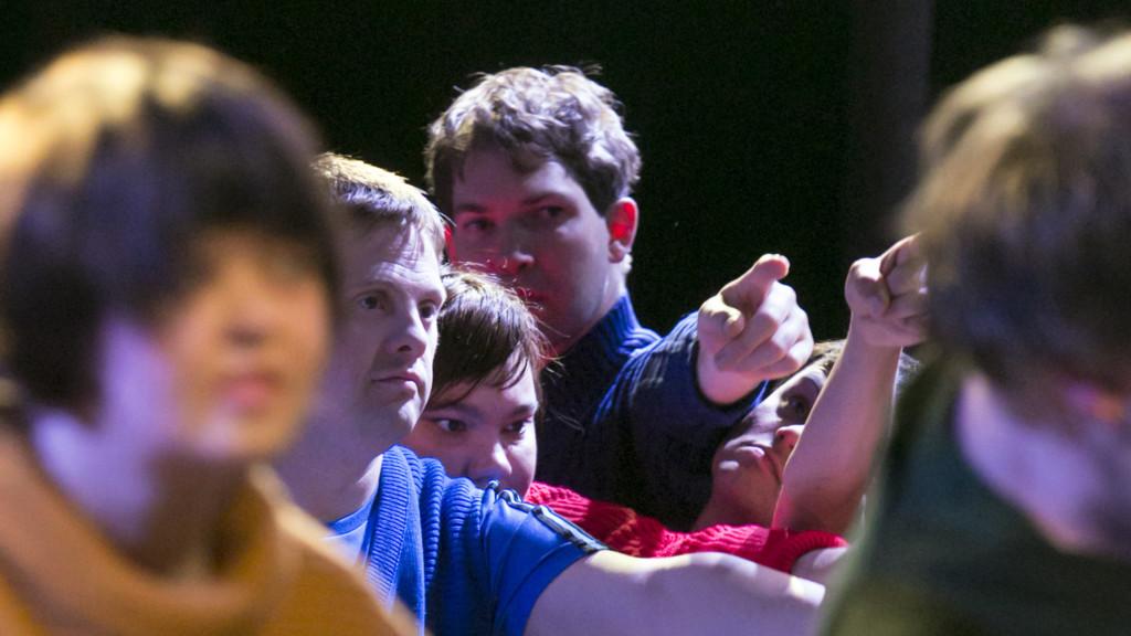 Szenenfoto aus einer Auffuehrung: Mehrere Menschen in Großaufnahme. Alle zeigen mit den Fingern in eine Richtung